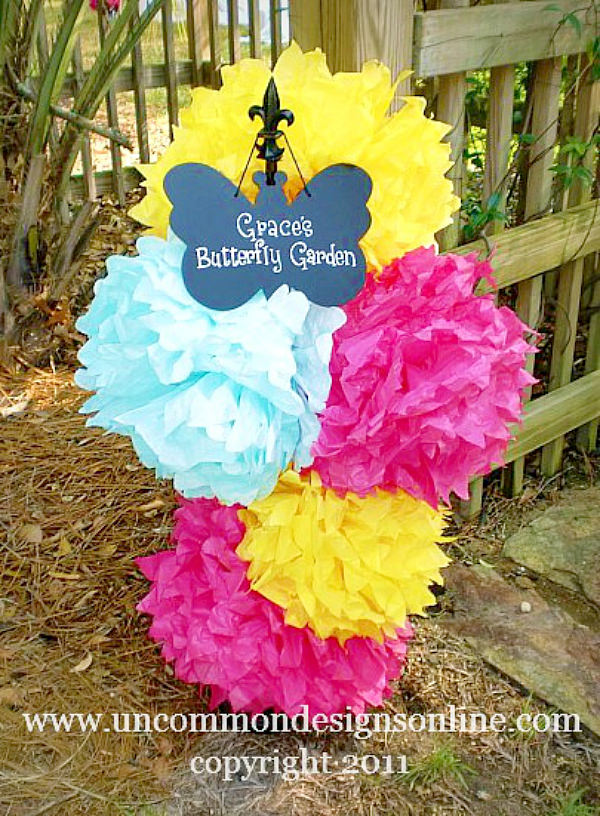 Paper Tissue pom poms as an entrance to a birthday party via Uncommon Designs.