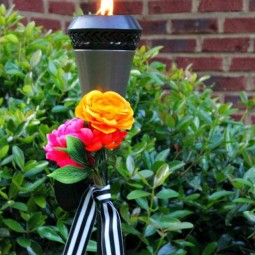 Dress up your tiki torches. These floral tiki torches would be gorgeous for a wedding or garden party. Add a few faux flowers and some striped ribbon and you are done! by Uncommon Designs