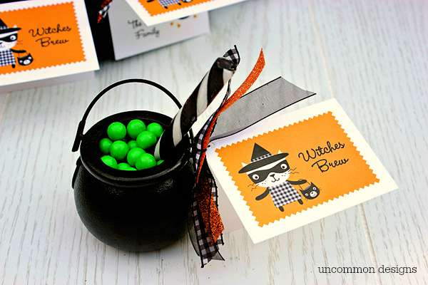 We decided to make witches brew treats out of miniature cauldrons and candies. We were able to pick up all of the supplies at our local craft store which was so convenient. We needed green Sixlet candies, miniature cauldrons, black and white striped candy sticks, and various ribbons. First, we tied the cards on to the handle of the cauldron with a fun assortment of Halloween ribbons, then we filled it up with the green candies for our brew and used the candy stick as our wooden stir stick. That is it… so cute and so easy! These make perfect classroom treats, too!