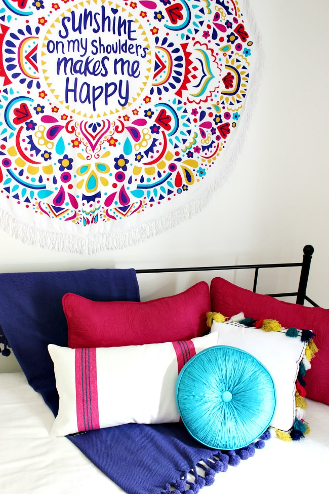 Boho Girls Room  with Benjamin Moore's Simply White, a colorful wall hanging, daybed with loads of gorgeous pillows | Uncommon Designs