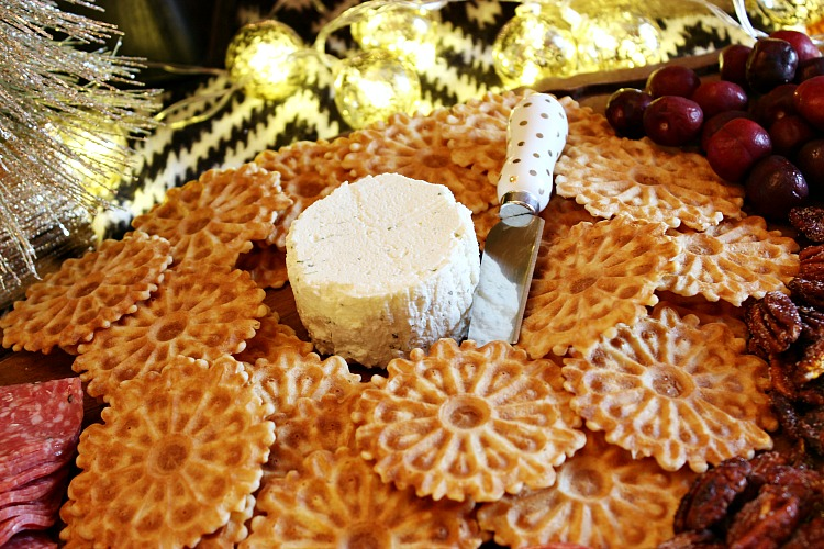 How to wow your guests with an upscale holiday appetizer board. Boursin gourmet cheese, crackers, nuts, salami and a sweet fruit make it a simple appetizer.