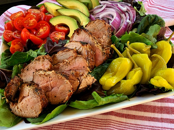 Fire up the grill for this delicious and cracked black pepper recipe for garlic and herb grilled pork tenderloin salad with loads of toppings. A great grilling recipe for summer!
