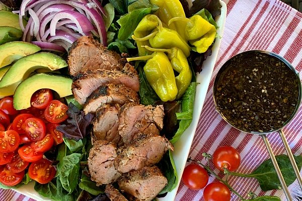 Fire up the grill for this delicious and light recipe for garlic and herb grilled pork tenderloin salad with loads of toppings. A great grilling recipe for summer!